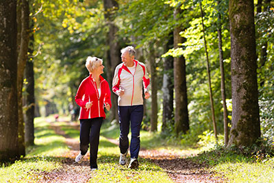 elderly couple walking through park in upland california